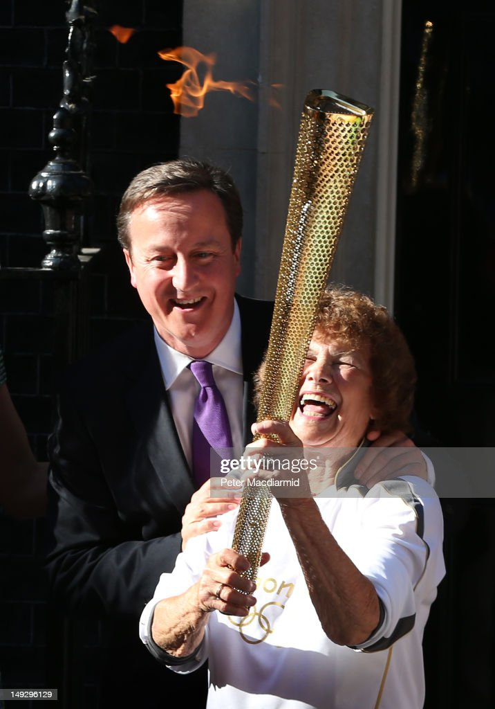 Prime Minister David Cameron stands with Olympic torch bearer Florence Rowe in Downing Street on July 26, 2012 in London, England. The torch relay will end tomorrow with it's arrival at the Olympic Park for the opening ceremony of the London 2012 Games.