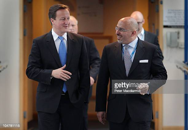 Prime Minister David Cameron walks with Conservative MP Nadhim Zahawi at the Conservative Party Conference during a television interview on October 5...