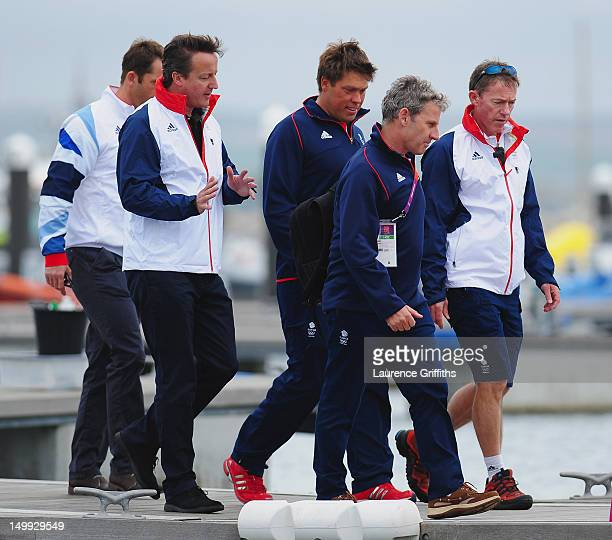 Prime Minister David Cameron walks with Finn class gold medallist Ben Ainslie and Star class silver medallist Andrew Simpson and John Derbyshire and...