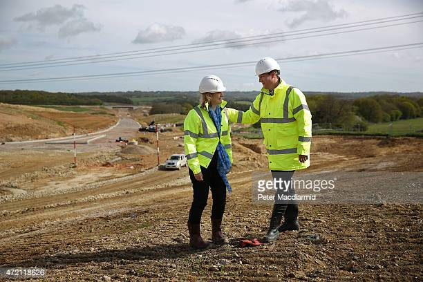 Prime Minister David Cameron walks with local Conservative party candidate Amber Rudd as they visit a road construction site on May 4 2015 near...