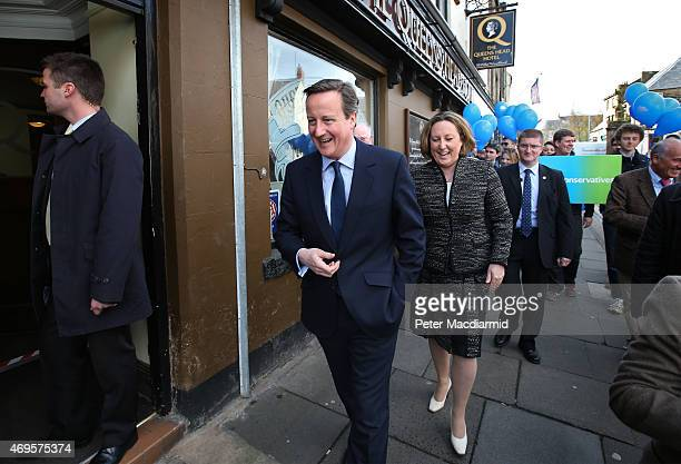 Prime Minister David Cameron walks with local parliamentary candidate AnneMarie Trevelyan as they campaigns on April 13 2015 in Alnwick England As...