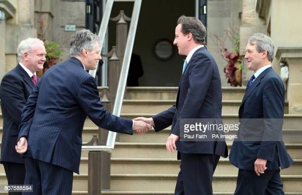 Prime Minister David Cameron, with Secretary of State for Northern Ireland Owen Paterson , is greeted by Democratic Unionist First Minister Peter...