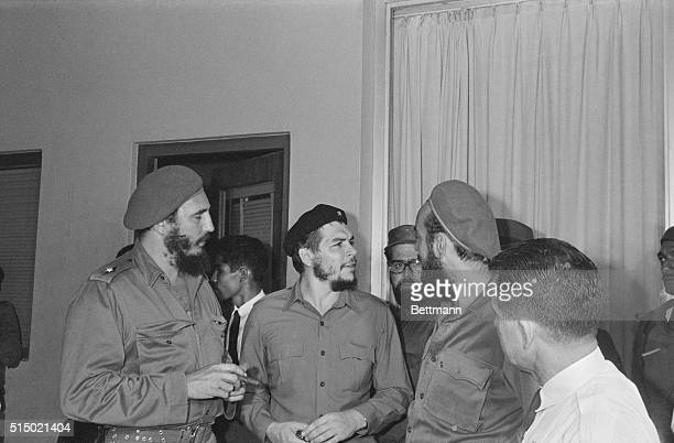 Prime Minister Fidel Castro and Captain Antonio Nunez listen here to Argentine born Major Ernesto Guevara Industry Minister before boarding a plane...