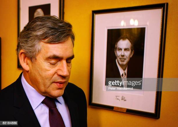 Prime Minister Gordon Brown walks past a picture of former Prime Minister Tony Blair in Downing Street on October 9 2008 in London England Brown is...