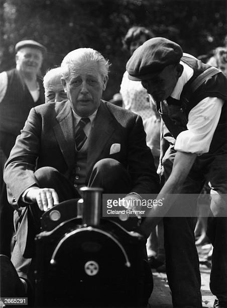 Prime Minister Harold MacMillan drives a miniature railway engine at a toy fair in Bromley, Kent where he is their local MP.