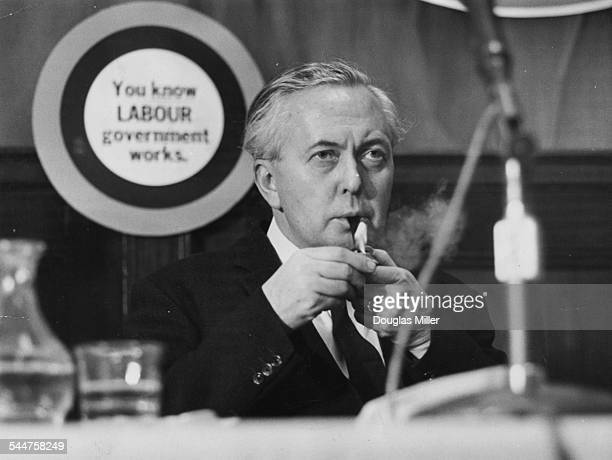 Prime Minister Harold Wilson lighting his pipe while one of his colleagues speaks at the Labour Party Conference prior to the General Election...