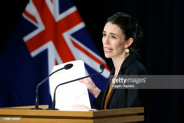 Prime Minister Jacinda Ardern holds up a list valid reasons for travelling across the Auckland border while speaking to media during a press...