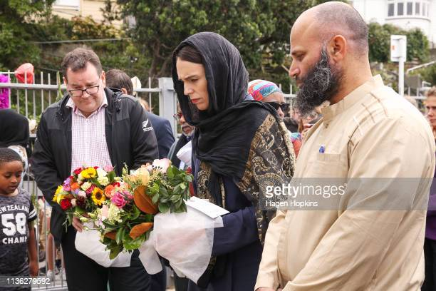 Prime Minister Jacinda Ardern lays flowers while finance minister Grant Robertson looks on at the Kilbirnie Mosque on March 17 2019 in Wellington New...