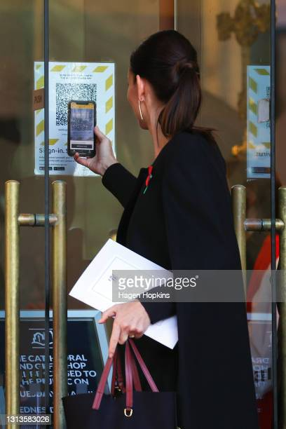 Prime Minister Jacinda Ardern scans a QR code with her mobile phone via the NZ COVID Tracer app at the State Memorial Service for Prince Philip, Duke...