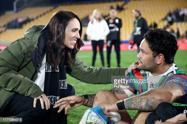 Prime Minister Jacinda Ardern stops to talke with Issac Luke of the Warriors who sits with his son Adaquix following the round 24 NRL match between...