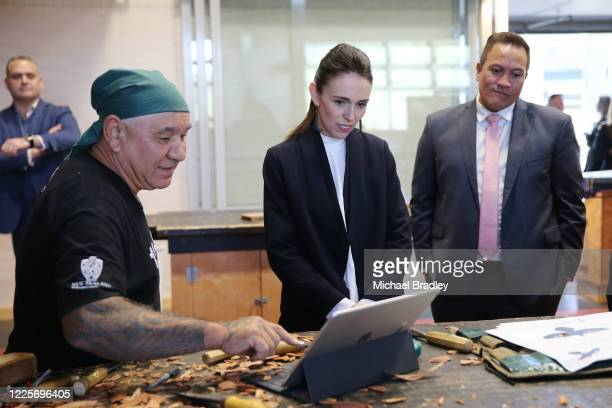 Prime Minister Jacinda Ardern talks with James Rickard Master Carver as MP Tamati Coffey looks on during a tour of Te Puia New Zealand Māori Arts and...
