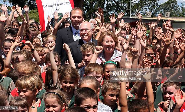 Prime Minister John Howard and wife Janette Howard pose with member for Dickson Peter Dutton and school students during a visit to Our Lady of the...