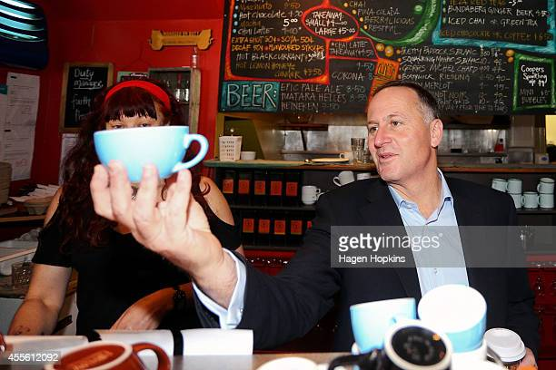 Prime Minister John Key holds a blue cup during a cafe visit as he begins his two days on the road for the National Party Bus Trip on September 18...