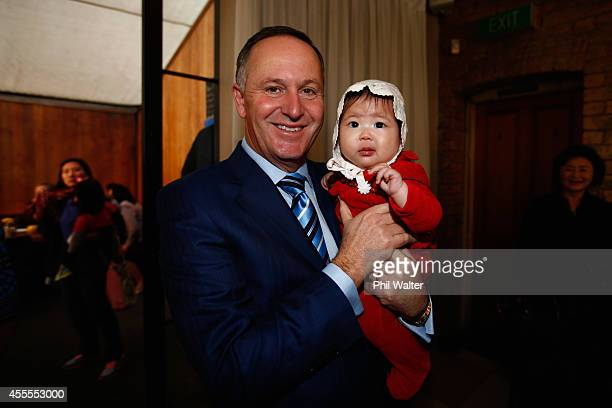 Prime Minister John Key holds a toddler after making a welfare policy announcement alongside Paula Bennett at Twenty Three Cafe on September 17 2014...