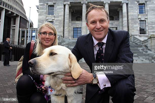 Prime Minister John Key poses with epilepsy assist dog Roxy and her owner Kate Hendra from Upper Hutt at Parliament on October 8 2012 in Wellington...