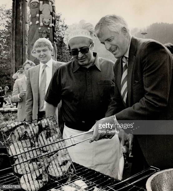 Prime Minister John Turner lends a helping hand in turning over Salmon Steaks during a BQ Held for his benefit while campaigning in Northern BC