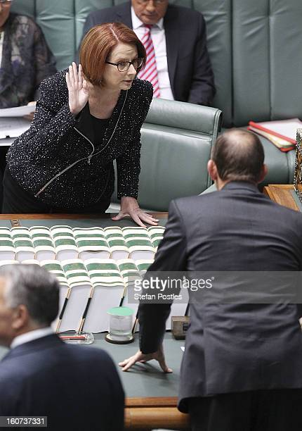 Prime Minister Julia Gillard and Opposition leader Tony Abbott speak prior to House of Representatives question time at Parliament House on February...