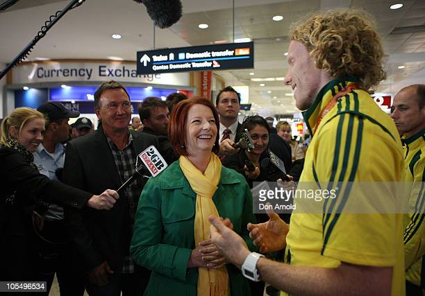 Prime Minister Julia Gillard greets Steve Hooker of the Australian Commonwealth Games team as it arrives at the Sydney International Airport on...