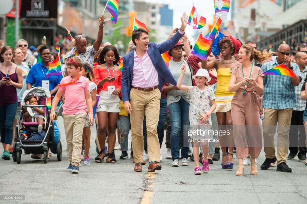 Prime Minister Justin Trudeau waves to the crowd as he, his wife Sophie Gregoire Trudeau and their children Xavier and Ella-Grace march in the Pride Parade in Toronto, June 25, 2017. /