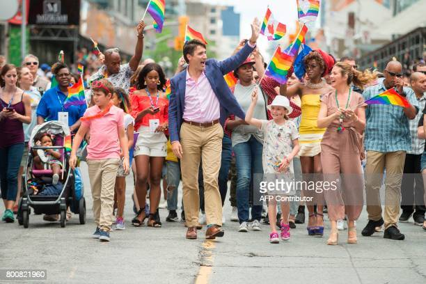 Prime Minister Justin Trudeau waves to the crowd as he his wife Sophie Gregoire Trudeau and their children Xavier and EllaGrace march in the Pride...