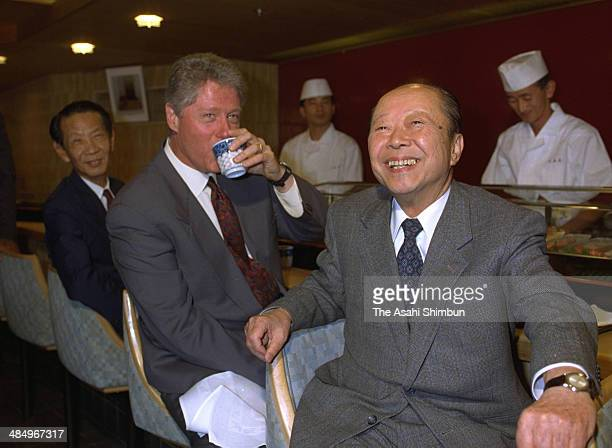 Prime Minister Kiichi Miyazawa and the US President Bill Clinton smile at a Sushi restaurant ahead of the summit meeting on July 9 1993 in Tokyo...