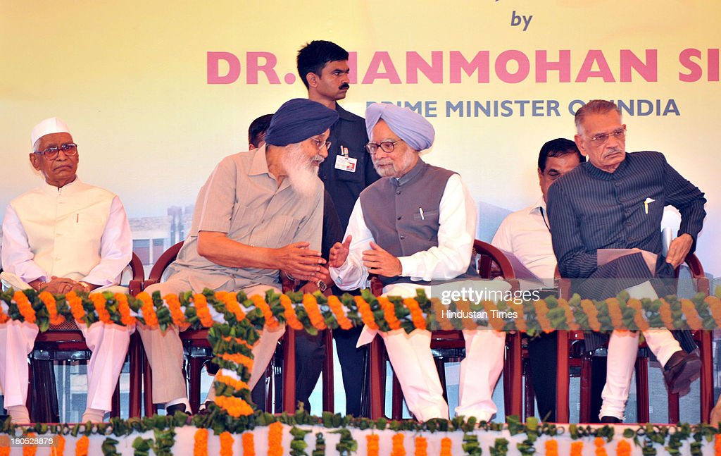 Prime Minister Manmohan Singh discussing on a point with Parkash Singh Badal Chief Minister of Punjab during the Slum Rehabilitation Scheme function..