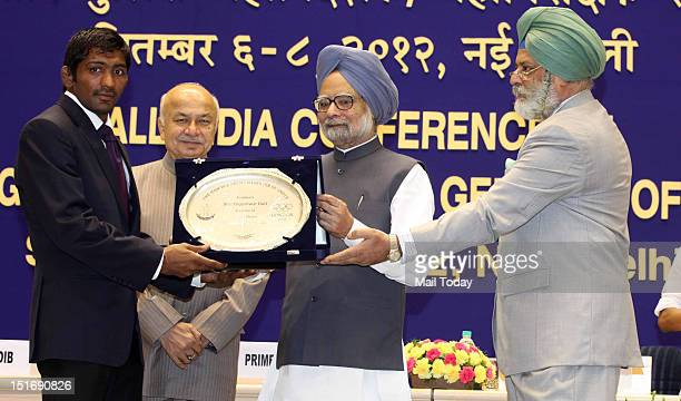 Prime Minister Manmohan Singh felicitates Olympic medallist Yogeshwar Dutt as Home Minister Sushil Kumar Shinde looks on at the All India Conference...