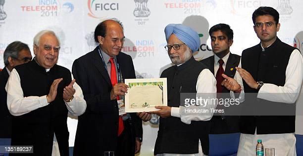 Prime Minister Manmohan Singh is presented with a certificate by FICCI President Harsh Mariwala and Union Minister for Communications IT Kapil Sibal...
