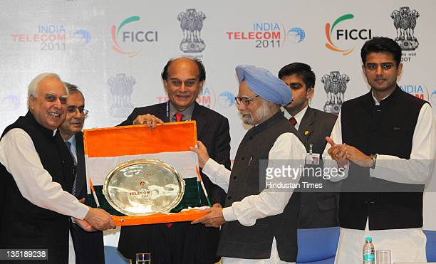 Prime Minister Manmohan Singh is presented with a memento by FICCI President Harsh Mariwala and Union Minister for Communications IT Kapil Sibal as...