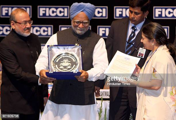 Prime Minister Manmohan Singh presenting the FICCI award for Outstanding Achievement In Environmental Sustainability of Businesses to Mrs Rajashree...