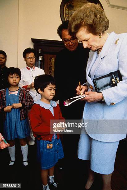 Prime Minister Margaret Thatcher signing autographs for children while visiting Hong Kong