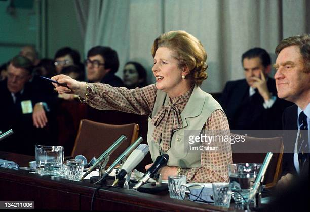 Circa 1980: Prime Minister Margaret Thatcher speaks beside her Press Secretary Bernard Ingham at a political conference during the early 1980s in...