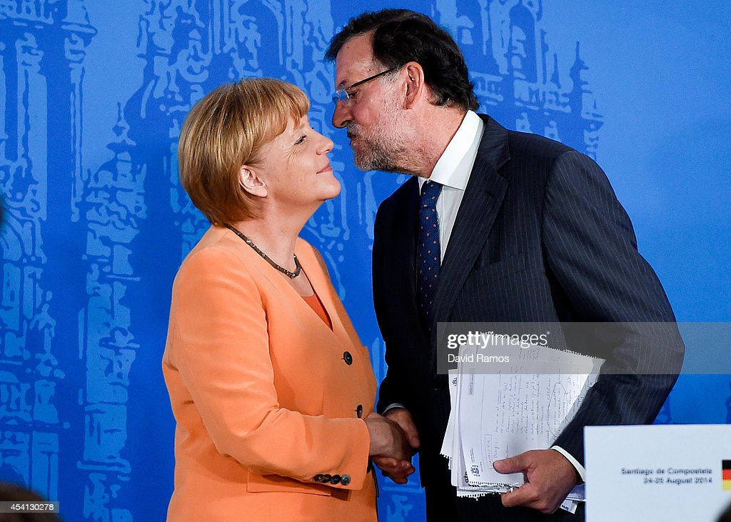 Prime Minister Mariano Rajoy kisses German Chancellor Angela Merkel at the end of a press conference as part of a two days summit on August 25, 2014 in Santiago de Compostela, Spain. German Chancellor Angela Merkel and Spanish Prime Minister Mariano Rajoy will hold an informal meeting to disscuss bilateral relations and unblocking negotiations for the election of the president of the Council and of the High Representative for the Foreign and Security Policy of the EU, ahead of an extraordinary European Council meeting that will be held in Brussels on August 30 .