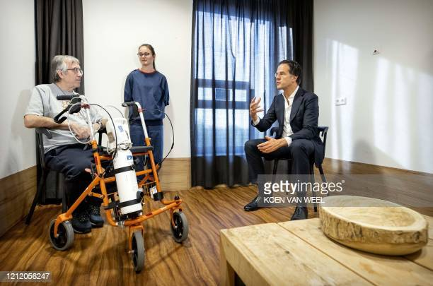 Prime Minister Mark Rutte talks to a patient during a visit to the Basalt rehabilitation center, on May 7, 2020 in the Hague, amid the crisis due to...