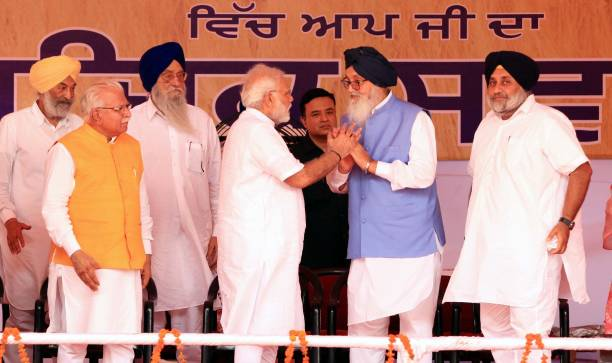 Prime Minister Narendra Modi and former Punjab Chief Minister Parkash Singh Badal shaking hands on stage during `thanksgiving` rally of farmers at...