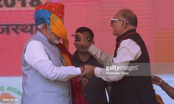 Prime Minister Narendra Modi being greeted with a turban that malfunctioned and rolled over PM's face by state party president Ashok Parnami at a...