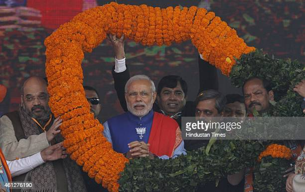 Prime Minister Narendra Modi felicitated with a huge garland during the 'Abhinandan rally' at Ramlila Maidan on January 10 2015 in New Delhi India...