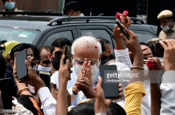 Prime Minister Narendra Modi gestures at supporters upon his arrival from the US, at Palam technical Airport, on September 26, 2021 in New Delhi,...