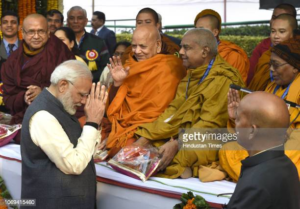 Prime Minister Narendra Modi greets Buddhist monks at a ceremony to pay homage to Bhimrao Ramji Ambedkar on his 62nd death anniversary at Parliament...