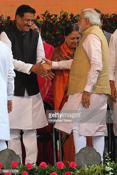 Prime Minister Narendra Modi greets former chief minister of Maharashtra Prithivraj Chavan during the swearingin ceremony of BJP leader Devendra...