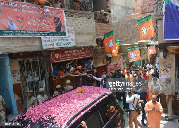 Prime Minister Narendra Modi greets party supporters as he leaves to file his nomination paper from Varanasi Lok Sabha parliamentary constituency...