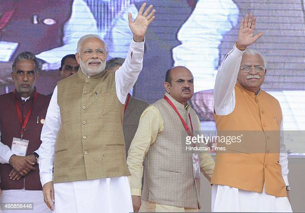 Prime Minister Narendra Modi Haryana Chief Minister Manohar Lal Khattar wave to the crowd at a public meeting during the foundation stone laying...