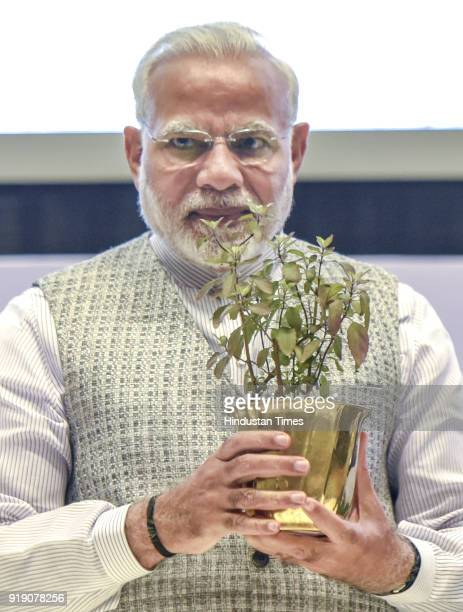 Prime Minister Narendra Modi holds a Tulsi Plant given to him during inauguration function of World Sustainable Development Summit at Vigyan Bhawan...