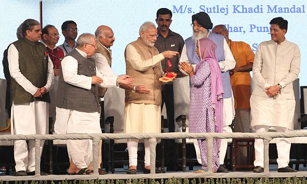 Prime Minister Narendra Modi honoring a lady during a function at PAU on October 18 2016 in Ludhiana India