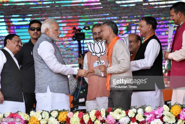 Prime Minister Narendra Modi introducing with Anil Sharma who join BJP last days after quit cabinet minister during an election rally at Jwahar Park...
