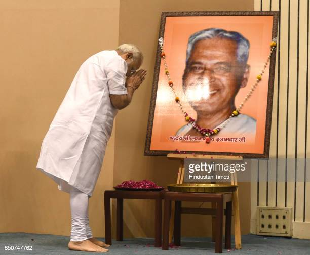 Prime Minister Narendra Modi pays floral tribute to the portrait of Laxman Rao Inamdar during his birth centenary celebration and Sahakar Sammelan on...