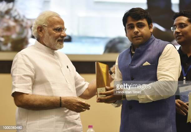 Prime Minister Narendra Modi presents a rural achievement award to a youth during the Y4D Foundation New India Conclave at Vigyan Bhavan on July 16...