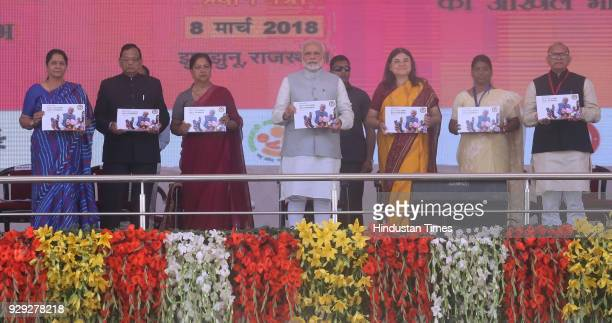 Prime Minister Narendra Modi releases a Photobook at a public rally at the launch of National Nutrition Mission on March 8 2018 in Jhunjhunu India...