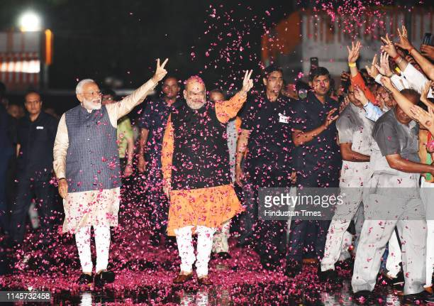 Prime Minister Narendra Modi shows victory sign as he along with the party President Amit Shah arrives at the party headquarters to celebrate their...