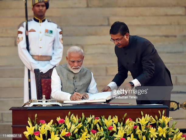Prime Minister Narendra Modi signs the documents after taking oath during a swearingin ceremony at the forecourt of Rashtrapati Bhavan on May 30 2019...